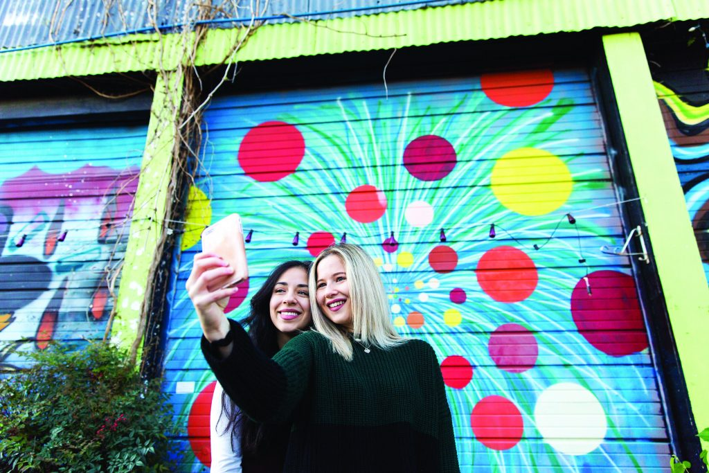 two women take a selfie in front of murals at railroad square art park