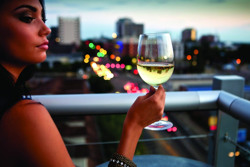 woman with glass of wine at Level 8 rooftop bar